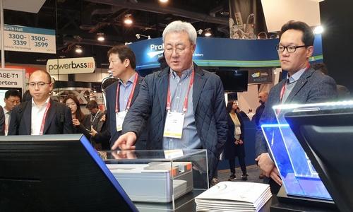 ▲ 김준 사장(가운데)이 8일(현지시각) SK그룹 부스에서 전시된 배터리 모듈을 살펴보고 있다.