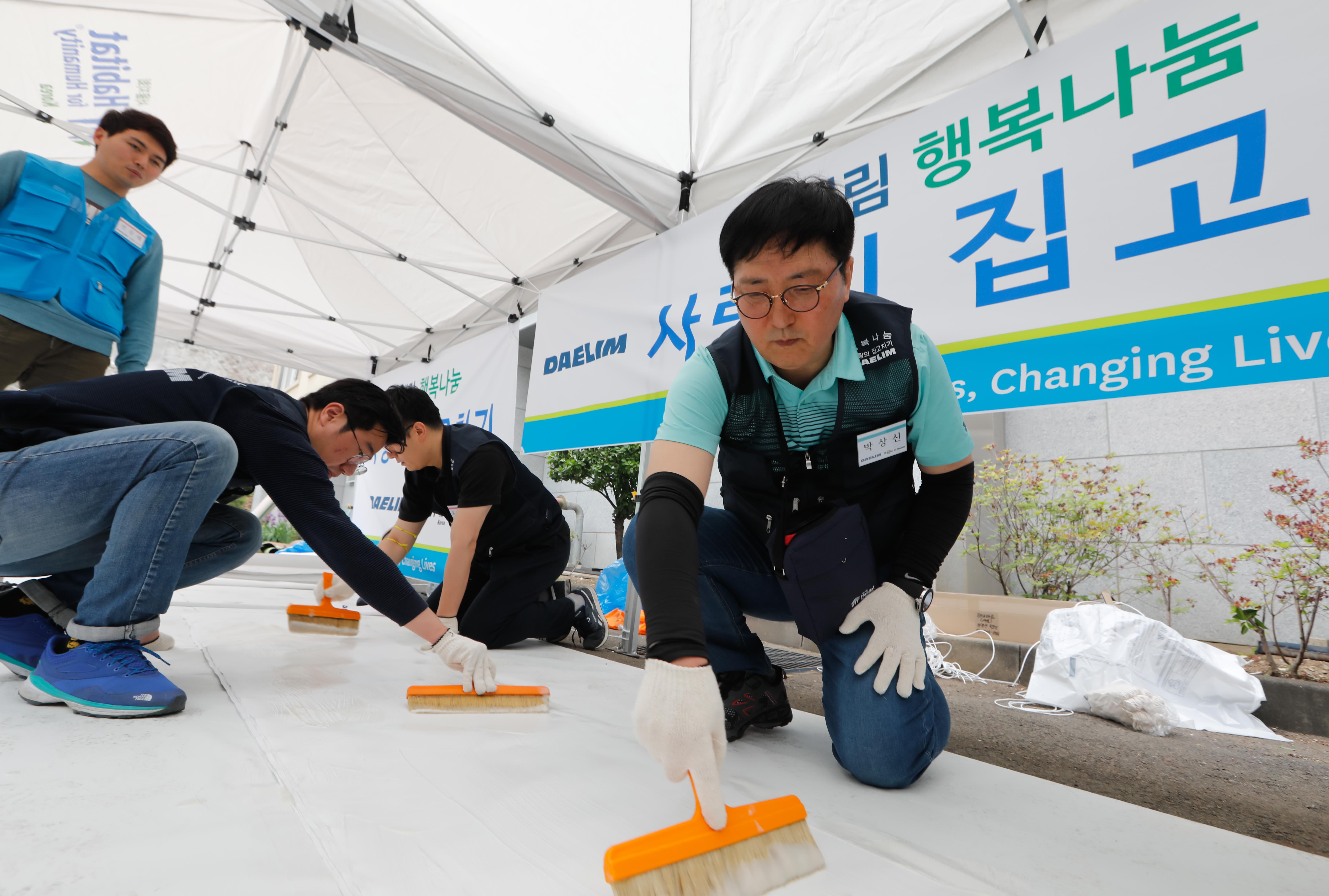 ▲ 대림산업 박상신 대표(우측 첫번째)가 도배작업에 사용할 벽지에 풀칠을 하고 있다